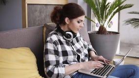 Ультрамодная девушка брюнет с компьтер-книжкой в ее руках плюхает на софе и начинает напечатать Hedphones на шеи самомоднейше видеоматериал