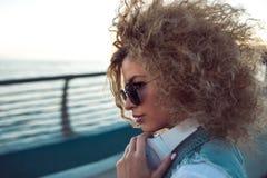 Ультрамодная девушка с большими наушниками и солнечные очки на городе идут, портрет молодой женщины в профиле стоковое изображение rf