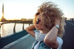 Ультрамодная девушка с большими наушниками и солнечные очки на городе идут, портрет молодой женщины в профиле стоковое изображение
