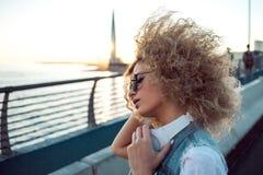 Ультрамодная девушка с большими наушниками и солнечные очки на городе идут, портрет молодой женщины в профиле стоковое фото