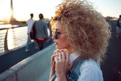Ультрамодная девушка с большими наушниками и солнечные очки на городе идут, портрет молодой женщины в профиле стоковая фотография
