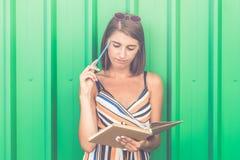 Ультрамодная женщина смотря тетрадь против зеленой стены стоковое фото