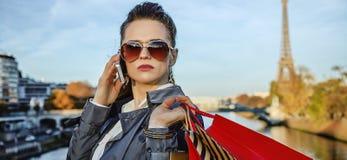 Ультрамодная женщина с хозяйственными сумками в Париже используя smartphone Стоковая Фотография RF