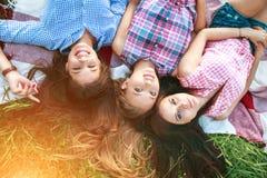 Ультрамодные девушки битника ослабляя на траве Портрет образа жизни лета 3 женщин битника кладя на траву наслаждается славным дне Стоковая Фотография RF