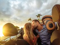 Ультрамодные молодые пары имея нежный момент в обратимом автомобиле во время их поездки - счастливый романтичный целовать даты но стоковые фото
