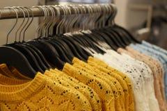 Ультрамодный Цейлон желтый и другие свитеры цвета шерстяные связанные вися на вешалках в магазине, конце-вверх стоковое изображение