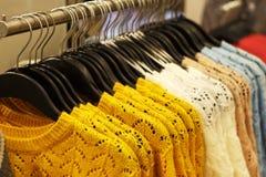 Ультрамодный Цейлон желтый и другие свитеры цвета шерстяные связанные вися на вешалках в магазине, конце-вверх стоковые фото
