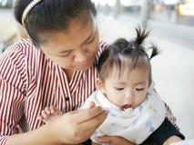 Умелая азиатская мать используя малую ложку для того чтобы подать ее ребёнок, 12 месяца старого, на столовой Стоковое фото RF
