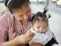 Умелая азиатская мать используя малую ложку для того чтобы подать ее ребёнок, 12 месяца старого, на столовой Стоковое Изображение