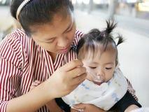 Умелая азиатская мать используя малую ложку для того чтобы подать ее ребёнок, 12 месяца старого, на столовой Стоковые Изображения RF