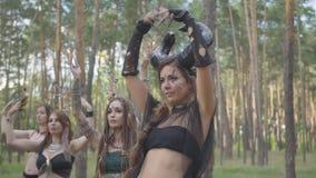 Умелые молодые женщины в театральных костюмах нимф леса танцуя в представлении показа леса или делая ритуал сток-видео