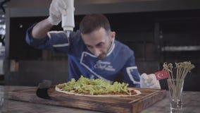 Умелый человек в форме повара подготавливая вкусное блюдо в оболочке в lavash Шеф-повар в белых резиновых перчатках лить листья с видеоматериал