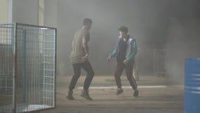 2 умелых молодые люди танцуя в темной и пылевоздушной комнате получившегося отказ здания Парни делая движения и представления тан видеоматериал
