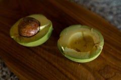 Уменьшанные вдвое авокадоы - взгляд сверху свежих фруктов получая отрезок на доске стоковое фото rf