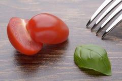 Уменьшанные вдвое томаты вишни и листья базилика на темной таблице Стоковые Фото