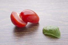 Уменьшанные вдвое томаты вишни и листья базилика на темной таблице Стоковые Изображения RF