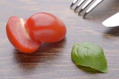 Уменьшанные вдвое томаты вишни и листья базилика на темной таблице Стоковое Изображение