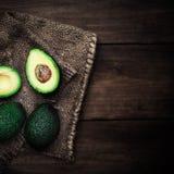 Уменьшанный вдвое авокадо на деревенской таблице Свежее palta авокадоа на черноте Стоковые Изображения RF