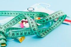 Уменьшая и dieting концепция с сантиметром связывает тесьмой и пилюльки стоковое фото rf
