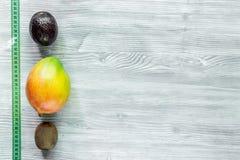 Уменьшение диеты Приносить манго, мангустан, киви и измеряя лента на сером copyspace взгляд сверху деревянного стола Стоковое Изображение RF