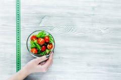 Уменьшение диеты Салат и измеряя лента на сером copyspace взгляд сверху предпосылки таблицы Стоковые Изображения