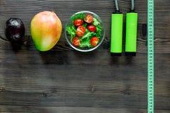 Уменьшение концепции Плодоовощи, салат, измеряя лента и прыгая веревочка на copyspace взгляд сверху деревянного стола Стоковое фото RF