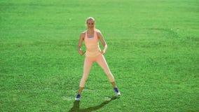 Уменьшите атлетическую женщину делая тренировки на зеленой траве видеоматериал
