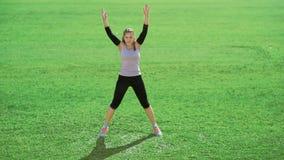 Уменьшите атлетическую женщину делая тренировки на зеленой траве сток-видео