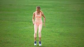 Уменьшите атлетическую женщину делая тренировки на зеленой траве акции видеоматериалы