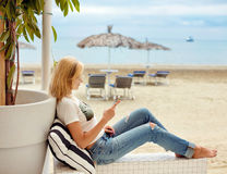 Уменьшите белокурую девушку в джинсах сидя и смотря телефон на ба стоковые изображения