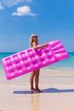 Уменьшите белокурую женщину с пляжем тропика тюфяка воздуха стоковое изображение
