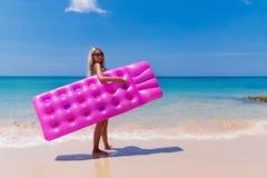 Уменьшите белокурую женщину с пляжем тропика тюфяка воздуха стоковые фотографии rf