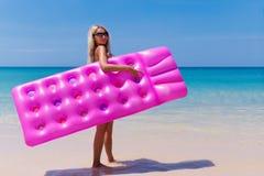 Уменьшите белокурую женщину с пляжем тропика тюфяка воздуха стоковое фото rf