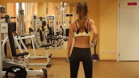 Уменьшите девушку спорт блондинкы практикуя в спортзале с гантелями