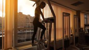 Уменьшите девушку спорт блондинкы практикуя на заходе солнца в спортзале в 4k