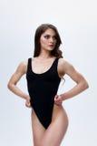 Уменьшите женскую модель в черном bodysuit на белой предпосылке стоковые фото