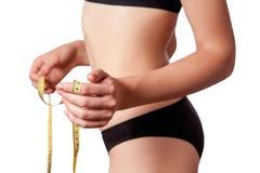 Уменьшите подходящую счастливую молодую женщину с измерять ленты измерения ее талия при черное нижнее белье, изолированное на бел Стоковые Фото