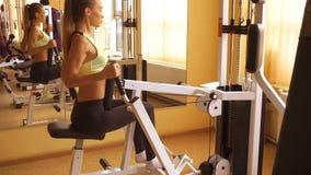 Уменьшите разминку женщины спорт блондинкы в спортзале в 4k