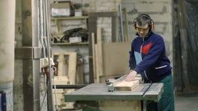 Умелая древесина вырезывания плотника используя круглую пилу сток-видео