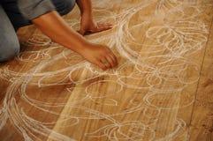 Умелые эскизы мастера высекая дизайн на древесине перед стартом высекая работу Стоковое Изображение