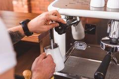 Умелый бармен сосредоточенно изучая сливк кофе от машины стоковая фотография