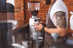 Умелый кофе заваривать бармена в столовой стоковые фотографии rf