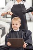 Умелый молодой парикмахер служит ее клиент Стоковые Изображения RF