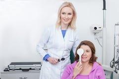 Умелый офтальмолог рассматривает человеческое зрение в офисе Стоковое Фото
