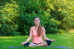 Умиротворянная женщина в розовой верхней части делая йогу в утре Стоковое Изображение