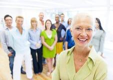 Умная дама с коллегами на заднем плане стоковое изображение rf