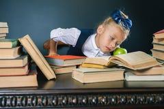 Умная девушка школы читая книгу на библиотеке Стоковое Изображение RF