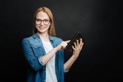 Умная женщина демонстрируя таблетку внутри помещения стоковое изображение