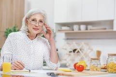 Умная зрелая женщина анализируя счета за коммунальные услуги Стоковое Изображение
