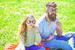 Умная и ухищренная концепция Папа и дочь сидят на траве на grassplot, зеленой предпосылке Ребенок и отец представляя с стоковая фотография